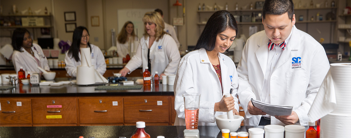students in lab coats compounding medicine in a classroom lab