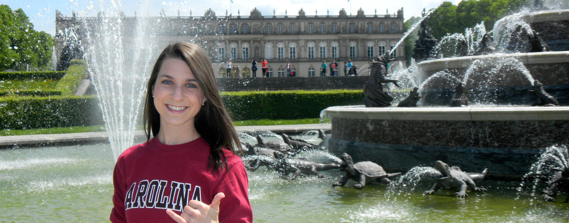 student posing in front of an outdoor fountain