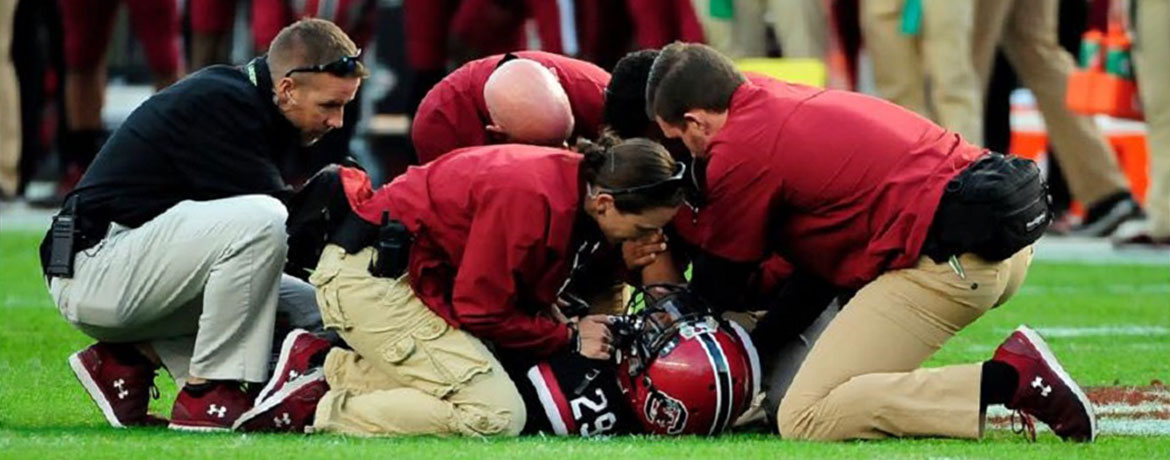 trainers helping a football player
