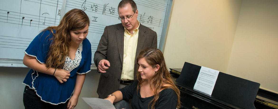 two music students consult with a professor in a practice room with piano and whiteboard