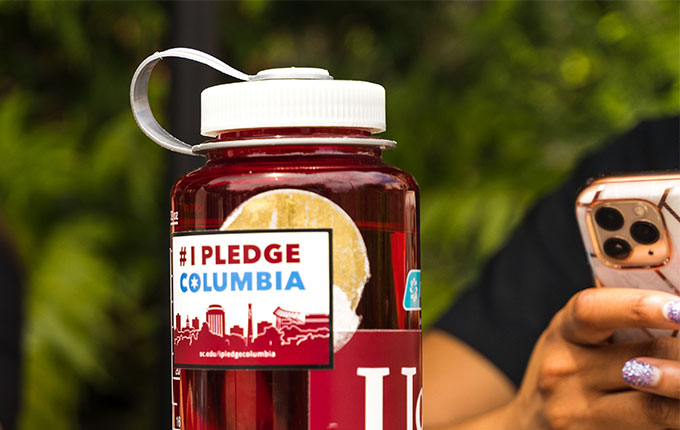 garnet water bottle with #IPledgeColumbia sticker and someone holding a phone