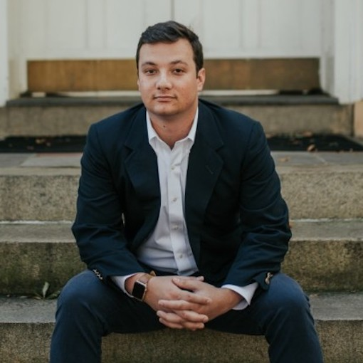 Cole Shubert sitting on steps with hands clasped