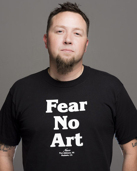 """Poet Ray McManus posing in a black and white shirt that says """"Fear no art."""""""
